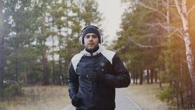 Uomo attraente del corridore in cuffie che pareggiano mentre musica d'ascolto nel parco di inverno di mattina Fotografie Stock Libere da Diritti