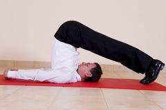 Uomo attraente di affari maturi che fa yoga Immagine Stock
