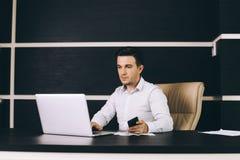 Uomo attraente di affari nell'abbigliamento casual astuto che si siede al suo posto di lavoro in ufficio Immagini Stock Libere da Diritti