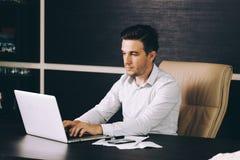 Uomo attraente di affari nell'abbigliamento casual astuto che si siede al suo posto di lavoro in ufficio Fotografia Stock Libera da Diritti