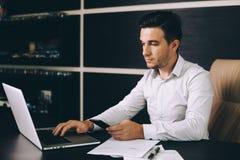 Uomo attraente di affari nell'abbigliamento casual astuto che si siede al suo posto di lavoro in ufficio Fotografie Stock
