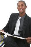 Uomo attraente di affari in vestito con il dispositivo di piegatura di archivio ed il grande sorriso Immagini Stock