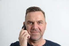 Uomo attraente di medio evo con il telefono cellulare Fotografie Stock Libere da Diritti