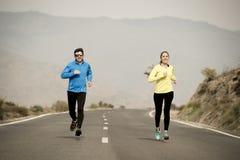 Uomo attraente e donna delle coppie di sport che corrono insieme sul paesaggio della montagna della strada asfaltata Fotografie Stock
