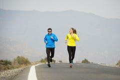 Uomo attraente e donna delle coppie di sport che corrono insieme sul paesaggio della montagna della strada asfaltata Immagine Stock