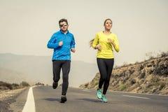 Uomo attraente e donna delle coppie di sport che corrono insieme sul paesaggio della montagna della strada asfaltata Immagine Stock Libera da Diritti