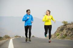 Uomo attraente e donna delle coppie di sport che corrono insieme sul paesaggio della montagna della strada asfaltata Immagini Stock Libere da Diritti