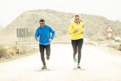 Uomo attraente e donna delle coppie di sport che corrono insieme sul paesaggio della montagna della strada asfaltata Fotografia Stock Libera da Diritti