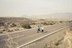 Uomo attraente e donna delle coppie di sport che corrono insieme sul paesaggio della montagna della strada asfaltata del deserto Fotografia Stock Libera da Diritti