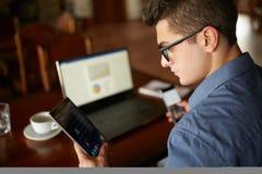 Uomo attraente nel funzionamento di vetro con i dispositivi di Internet elettronici multipli L'uomo d'affari delle free lance ha  immagini stock