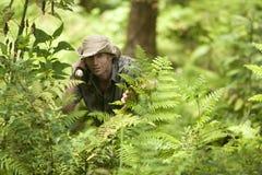 Uomo attraverso la foresta fotografie stock