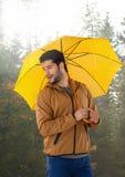 Uomo in autunno con l'ombrello in foresta Fotografia Stock Libera da Diritti
