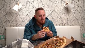 Uomo barbuto in accappatoio verde in camera da letto sul letto mangiare pizza per goderla movimento lento stock footage