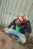 Uomo barbuto accovacciato con la mano in capelli Fotografie Stock