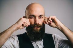 Uomo barbuto adulto che volteggia i suoi baffi delle dita Immagine Stock