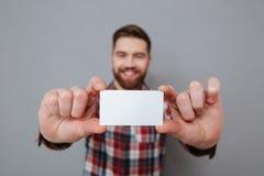 Uomo barbuto attraente che mostra il biglietto da visita del copyspace Immagine Stock Libera da Diritti