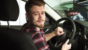 Uomo barbuto attraente che sorride alla macchina fotografica sopra la sua spalla che si siede in una nuova automobile immagini stock libere da diritti