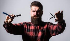 Uomo barbuto, barba lunga, pantaloni a vita bassa brutali e caucasici con i baffi Forbici del barbiere e rasoio diritto, negozio  immagini stock