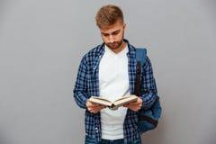 Uomo barbuto bello in camicia a quadretti con il libro di lettura dello zaino Fotografia Stock