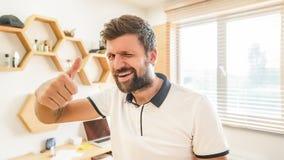 Uomo barbuto bello che dà strizzatina d'occhio che mostra pollice su fotografia stock