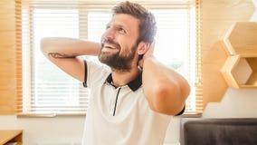 Uomo barbuto bello che ride tenendo le sue mani sul suo collo immagini stock