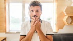 Uomo barbuto bello con espressione facciale che ride tenendo la sua mano sulla bocca immagine stock