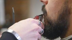 Uomo barbuto bello del primo piano giovane che ottiene barba che governa nel parrucchiere moderno video d archivio
