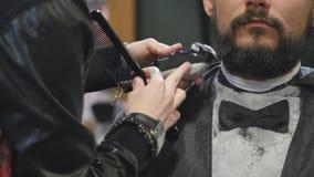 Uomo barbuto bello del primo piano giovane che ottiene barba che governa nel parrucchiere moderno archivi video