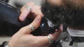 Uomo barbuto bello del primo piano giovane che ottiene barba che governa nel parrucchiere moderno stock footage