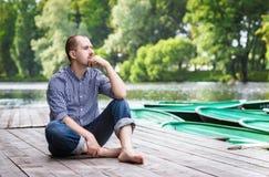 Uomo barbuto bello giovane che si siede sul pilastro di legno, sul rilassamento e sul pensiero Fotografia Stock