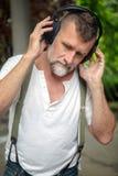 Uomo barbuto bello nel suo 50s con le cuffie Immagini Stock Libere da Diritti