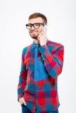 Uomo barbuto bello sorridente in vetri che parla sul telefono cellulare Fotografia Stock