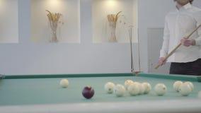 Uomo barbuto biondo che gioca stagno, biliardo nella stanza leggera Il giocatore sicuro colpisce la palla con un'indicazione Stag video d archivio