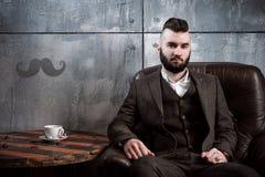 Uomo barbuto brutale con la barba che posa, whiskey bevente fotografia stock libera da diritti