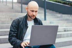 Uomo barbuto calvo riuscito adulto di pensiero in rivestimento nero facendo uso del computer portatile in scale alla città fotografia stock