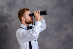 Uomo barbuto in camicia e farfallino bianchi davanti al backgro grigio Immagine Stock Libera da Diritti