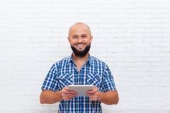 Uomo barbuto casuale che usando sorriso felice del computer della compressa Immagini Stock Libere da Diritti