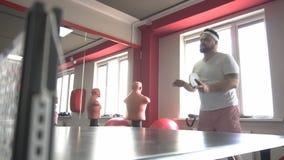 Uomo barbuto caucasico grasso che gioca ping-pong in una palestra moderna, scaricante peso in eccesso, movimento lento stock footage