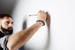 Uomo barbuto che drawning sui precedenti vuoti della parete fotografie stock
