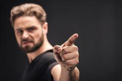 Uomo barbuto che indica sul nero con lo spazio della copia fotografia stock