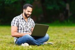 Uomo barbuto che lavora all'aperto sul computer portatile fotografia stock libera da diritti