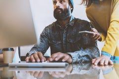 Uomo barbuto che lavora nell'ufficio Collega che scrive ad una tastiera di computer Donna che sta vicino lui e che tiene smartpho Immagini Stock