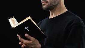Uomo barbuto che legge bibbia santa, pregante Dio contro il fondo scuro, salmo stock footage
