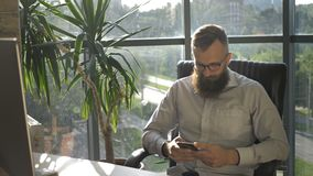 Uomo barbuto che manda un sms nel telefono cellulare in sottotetto moderno che coworking archivi video