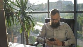Uomo barbuto che manda un sms nel telefono cellulare in sottotetto moderno che coworking video d archivio
