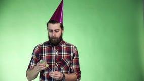 Uomo barbuto che mette su un cappello del partito stock footage