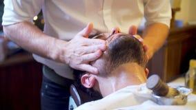 Uomo barbuto che ottiene taglio di capelli della barba e raso archivi video