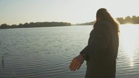 Uomo barbuto che pesca con la canna da pesca che sta sulla banca del fiume Il pescatore getta la barretta nel fiume Fiume stock footage
