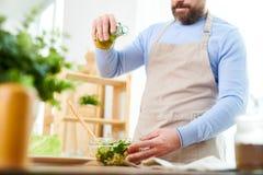 Uomo barbuto che prepara insalata di verdure immagini stock