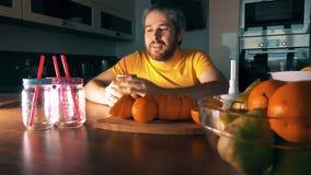 Uomo barbuto che produce e che beve succo d'arancia fresco a casa stock footage